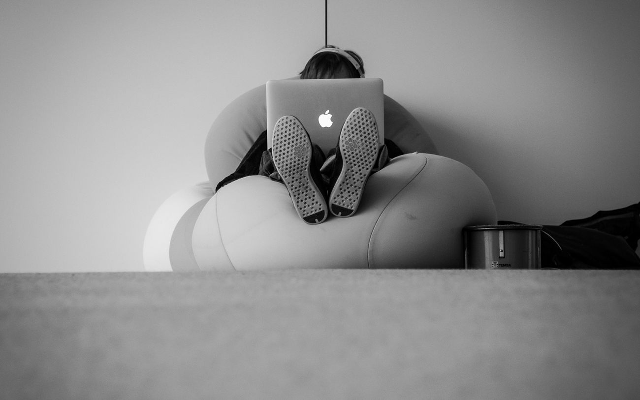 ソファーでMacを見る人