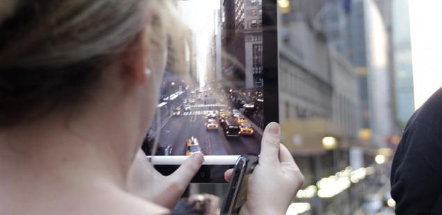 タブレットのカメラで街を撮る女性