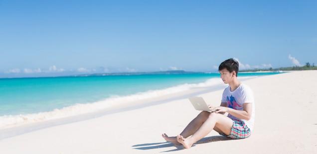 海辺でMacを使う男性