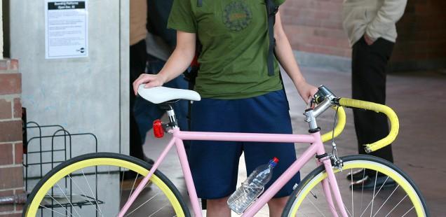 ヘルメットをかぶって自転車を持つサイクリスト