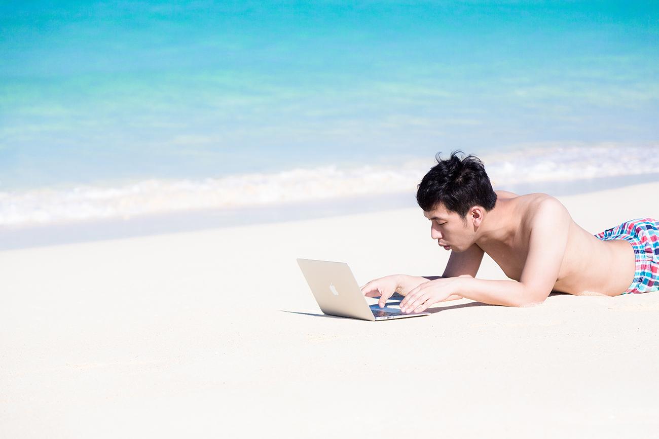 砂浜でMacBook Airで仕事をする男性