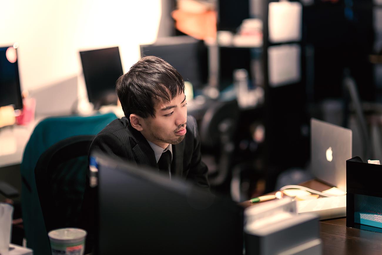 オフィスで残業する男性