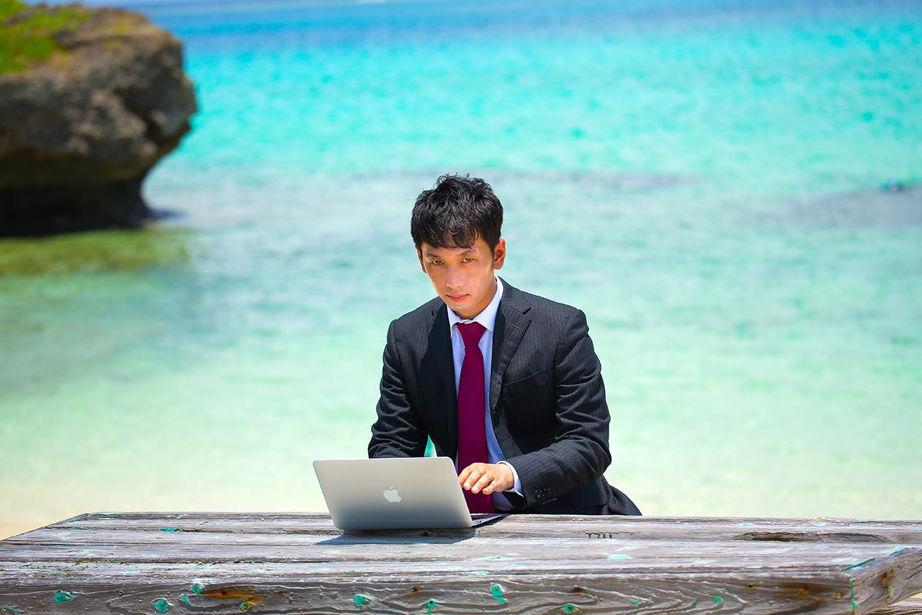 海でMacBook Proを使うスーツの男性