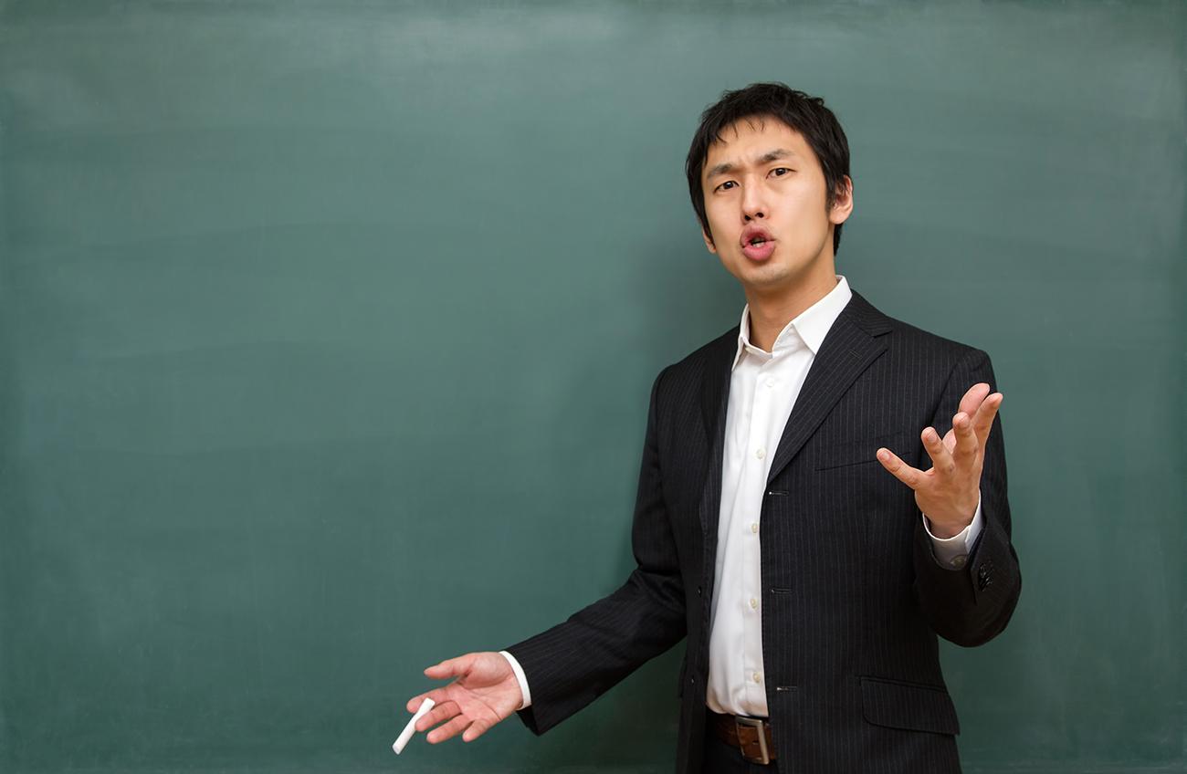 黒板の前の男性教師