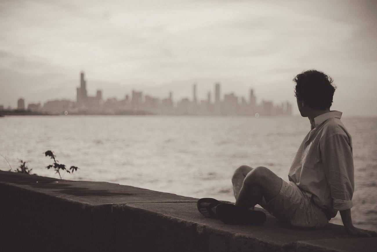 海から街を見る男性
