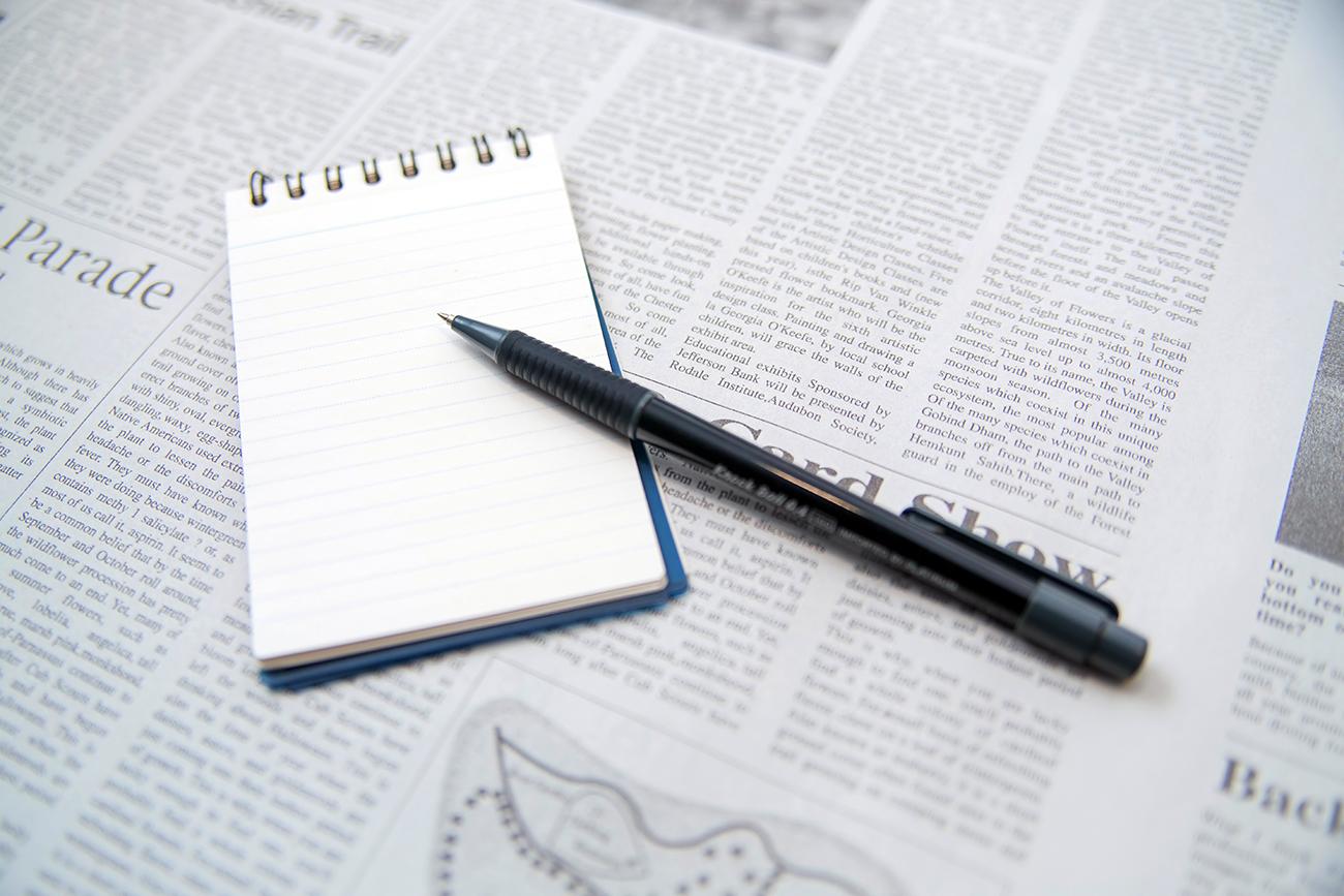 英語の原稿と紙とペン