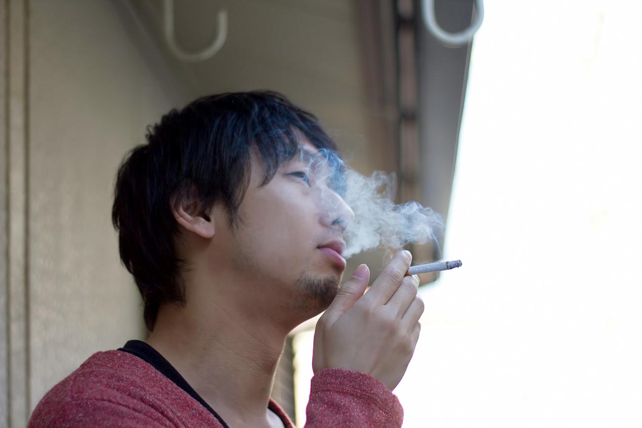 ベランダでタバコを吸う男性