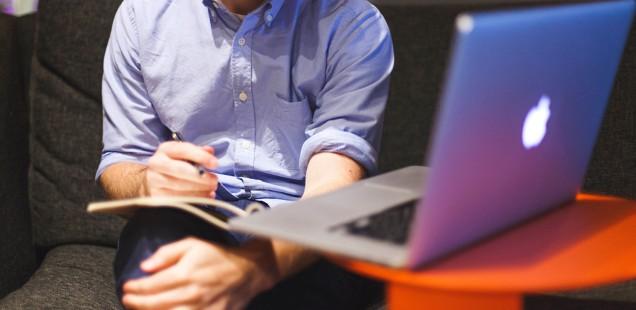 ノートを持った男性とMacBook Pro
