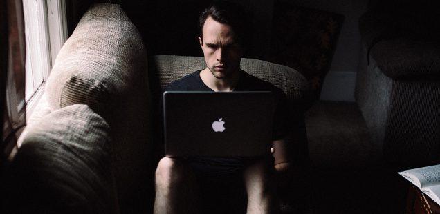 暗い部屋でMacを使う男性