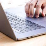 MacBook Proのトラックパッドを触る手