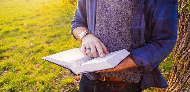 草原で読書をする男性